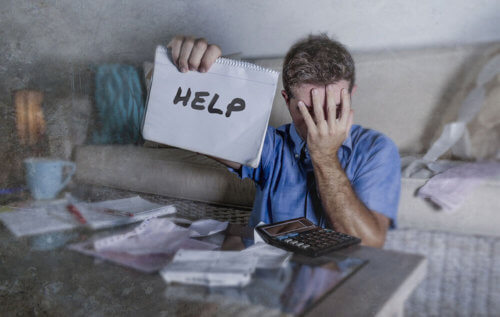 Man covers his face in shame while holding up a sign for help with his finances