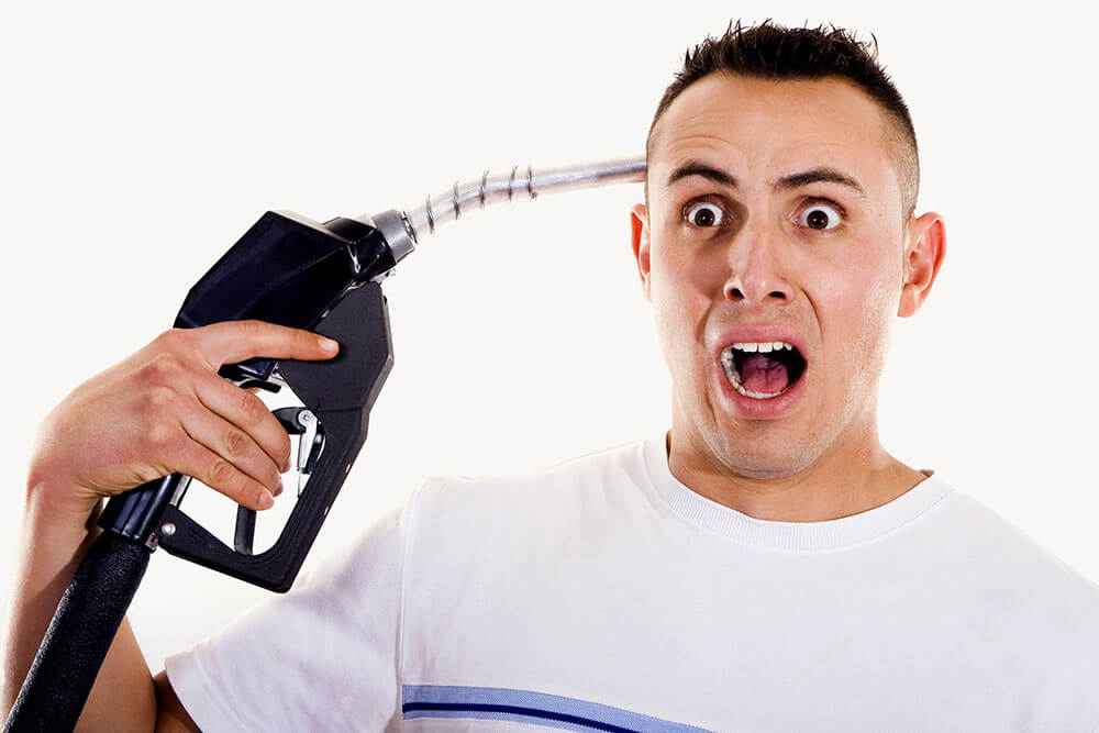 Man holds petrol pump to his head as a gun symbolising the increase in petrol price and the effect it has on consumers