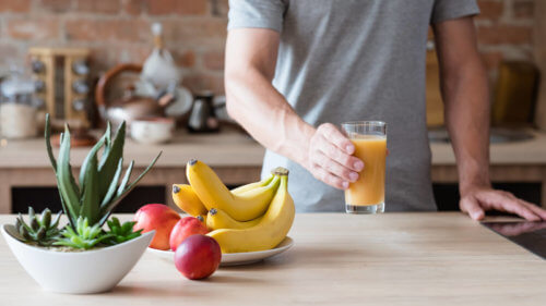 Through small changes, such as meal planning, we can save a lot of money. A man holds a glass of orange juice standing next to fresh fruit.