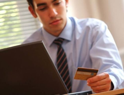 Man looking at credit card sitting behind his computer contemplating buying on credit again.